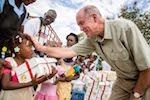 Cross Catholic Outreach CEO Jim Cavnar talks to a young Haitian girl receiving her first Box of Joy at her school in Beganabe Village. Photo courtesy of Cross Catholic Outreach