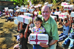 In the Santa Rosa area as children raise high their new Boxes of Joy, Cross Catholic Outreach CEO Jim Cavnar poses with a young Guatemalan girl. Photo courtesy of Cross Catholic Outreach