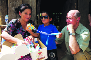 Sofia Cortez and her son, Manfred, show off his new glasses and toys to Cross Catholic Outreach CEO Jim Cavnar in La Concepción, Guatemala. Photo courtesy of Cross Catholic Outreach